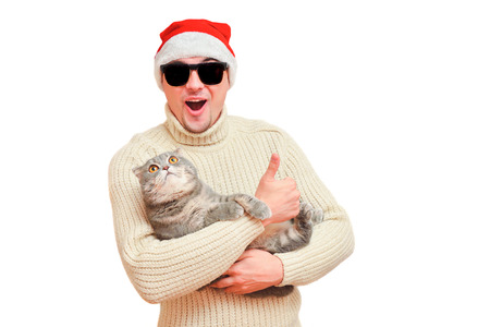 advertizing: Man in Santas cap in sunglasses with a cat on hands tells super. Very ridiculous person with a joyful astonished face.