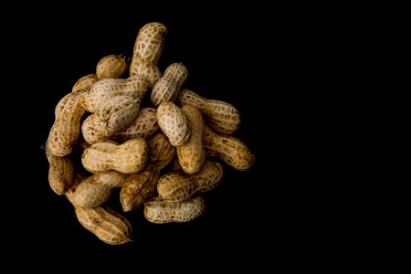 Heap of nuts on black background. Top view with copy space.