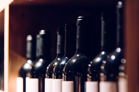 Wine bottles in the dark room. Regiments with wine bottles. Glass bottles, focus on one bottle.