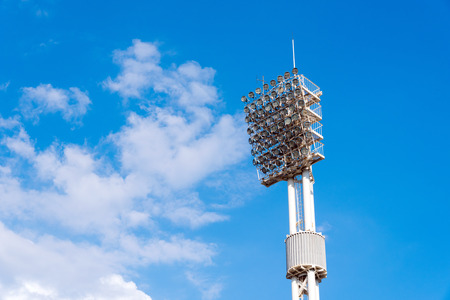 Lighting tower with lamps at stadium. Lighting fixtures at stadium. A column against the background of the blue sky.