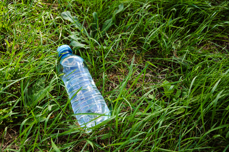 Plastic bottle with water on a green grass