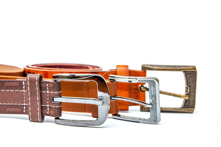 Accessories of mens wear leather belts on a white background. Mens leather belts on a white background with different buckles.