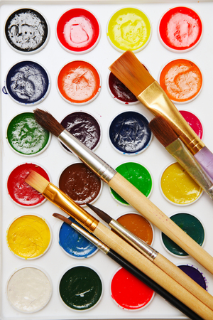 Brushes for drawing paints on a background of watercolor paints Stock Photo