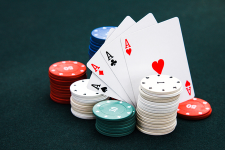Four cards aces of different stripes and casino chips Stock Photo