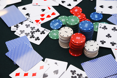 Casino game. Cards and playing chips on the table are scattered chaotically Stock Photo