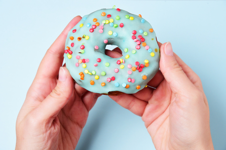 Delicious donut covered with blue glaze in female hand on blue background