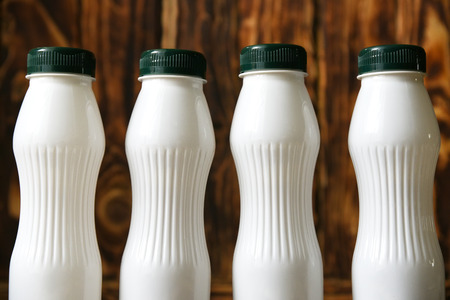 White plastic milk bottles on a wood background Archivio Fotografico - 101540484