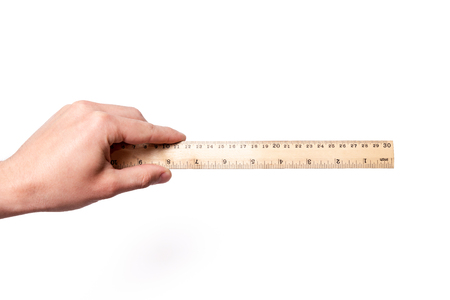 Concept measure tool, ruler measurement. Man hand hold the wood rule on white background isolated Zdjęcie Seryjne