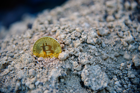Catch bitcoin in ground, golden coin in ground conceptual close up macro commerce symbol