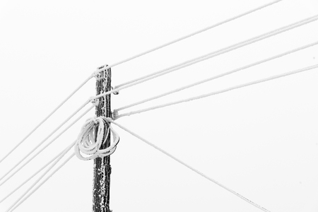 Electrical Power pole with wires in the winter frost. Freezing high-voltage line. Frozen Electrical Power wire.