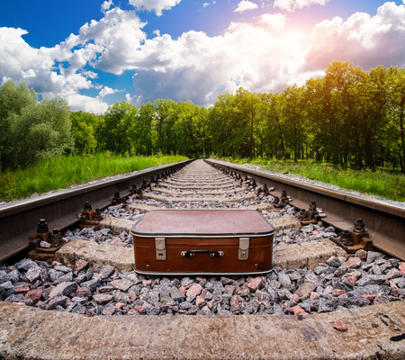 Suitcase on railway on summer forest. Concept of trip and adventure