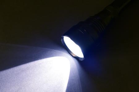 Laternentaschenlampe mit hellem Licht in einem dunklen Raum. Lichtstrahl der Taschenlampe.