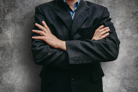 Close up business man in a suit near the concrete wall. Man with crossed arms Stock Photo