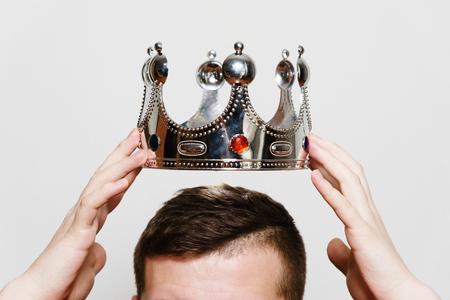 Incoronazione. Vestire la corona sulla testa. Concetto di affari - responsabile di appuntamento. Mani dell'uomo che tengono la corona sopra la sua testa, su sfondo grigio chiaro, in studio.