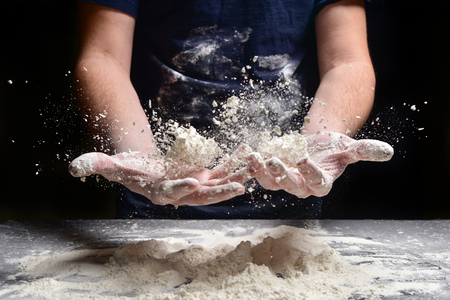 Male hands prepare bread, pie, pizza from flour. Hands cook throw flour. Фото со стока