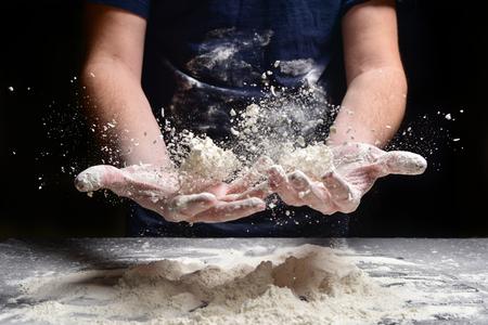 Male hands prepare bread, pie, pizza from flour. Hands cook throw flour. 版權商用圖片