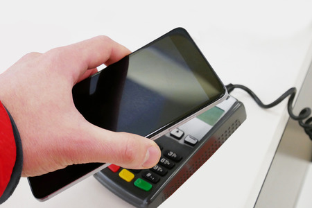 Payment by smartphone, paying with NFC technology. Contactless payment for goods. Man making a contactless smartphone payment Banco de Imagens