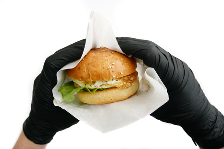 Hand in black gloves hold burger on white background. Fast food concept, unhealthy diet, junk food