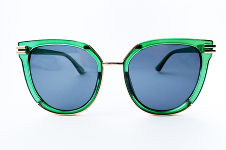 Sun glasses in green plastic rim on white background