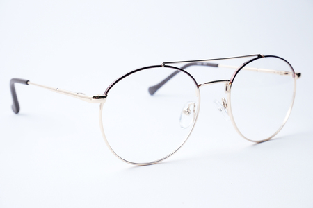 Round glasses for sight on a white background. Glasses with gold metal rim.