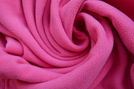 Fabric of pink color woolen clothes background in spiral shape with waves.