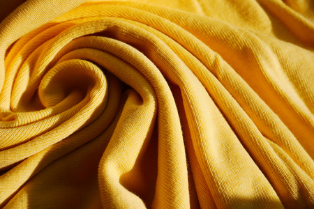 Yellow bright wool clothing wave backdrop surface.