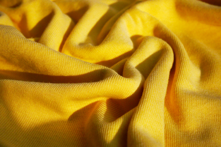 Texture of yellow fabric with waves. Fabric yellow color background.