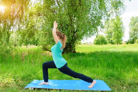 Beautiful girl practices yoga in park. Sunny summer day.