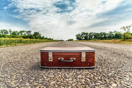 Old suitcase on the road