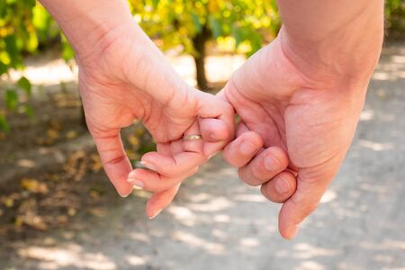 Man and woman hold hands. Hands of a couple finger by finger close-up. 版權商用圖片
