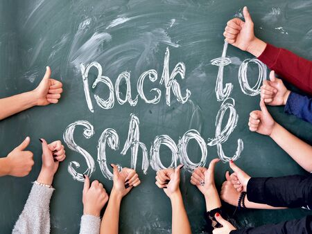 Students hands show thumbs up on the background of the inscription back to school in chalk on a school blackboard. Team education at school. 版權商用圖片