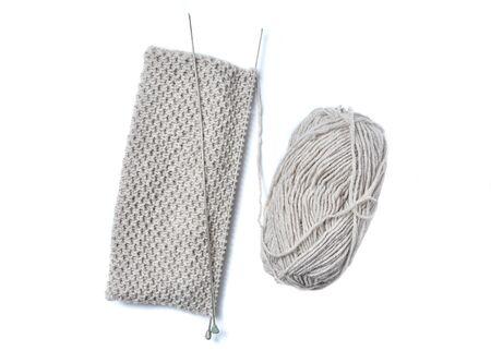 Fili di lana e ferri da maglia, pezzo di maglia grigia. Archivio Fotografico