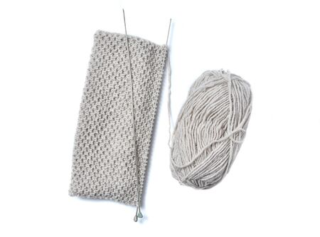 Woolen threads and knitting needles, piece of grey knitting. Фото со стока