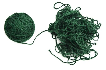 Ball of green fine wool ball thread and tangled thread on white background
