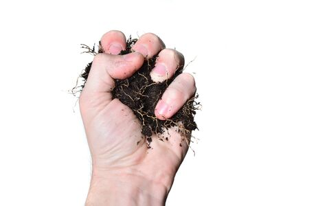 Farmer's male hand holds the soil on a white background