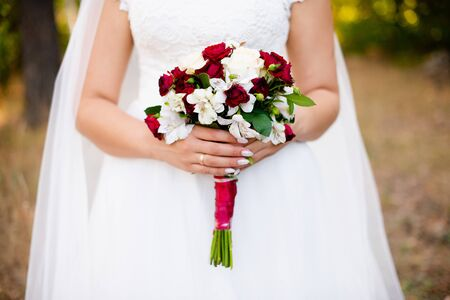 Bride holding wedding bouquet on wedding ceremony in hand