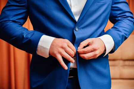 Man fastens a button on his jacket. Male arm and finger close up 写真素材