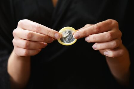 Girl hold in hand a condom close up. Propose contraception for sexual partner.