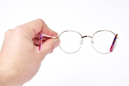 Vision care. A look through the glasses. Diopter checks on lenses with glasses. A man holds glasses in his hand on a white background. 写真素材