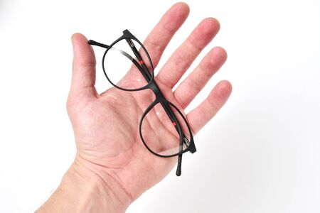 Glasses rim in man hand on white background. Bad vision concept.