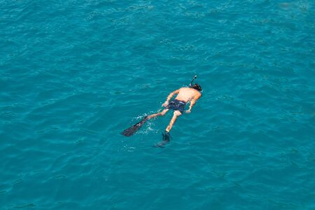 Man swims in the sea with a snorkel and a mask, diving. 写真素材