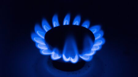 Burning blue gas on a black background. Gas burner on the stove close-up 写真素材