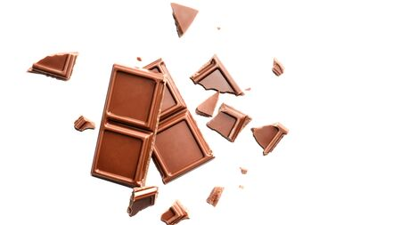 Pieces of broken milk chocolate on a white background