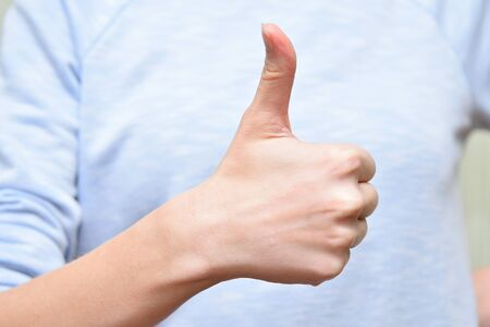 Girl show thumb up sign. Human body part positive gesture. 写真素材