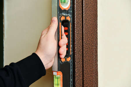 Professional measuring equipment. Worker hold in hand spirit level instrument.
