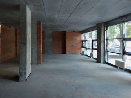 Large empty room inside after construction, repair with large windows.