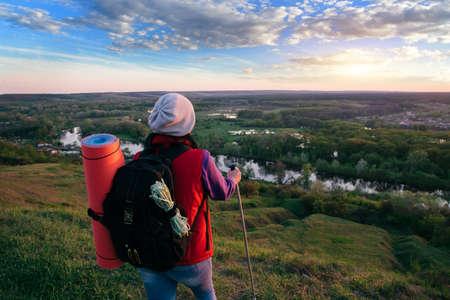 Travel lifestyle woman hiking at sunset mountains.