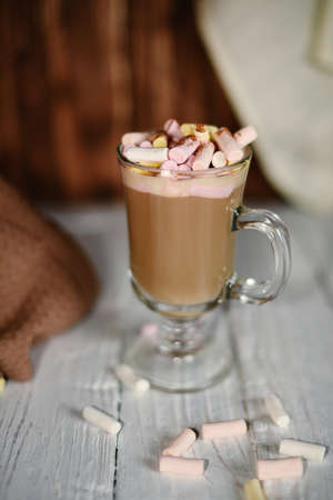 Glass coffee cup with marshmallow on whote wood table