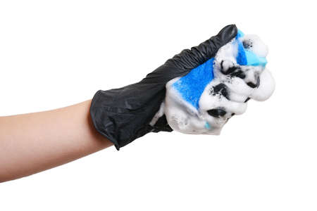 Work at home, washing dishes. A hand in a black glove holds a sponge with foam.