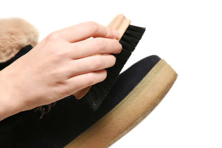 Shoe cleaning, shoe care. Girl hand brushing shoes close-up Фото со стока